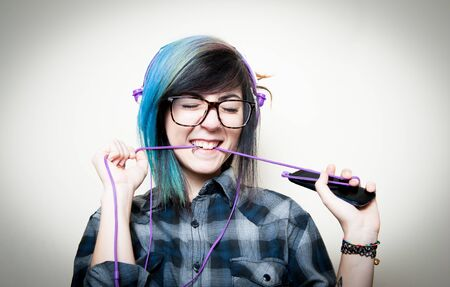head phones: Pretty young teen woman with mobile phone happy while listening music with head phones