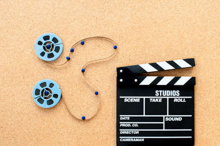 super 8: Two little blue movie reel connected with filmstrip path on wooden cork board