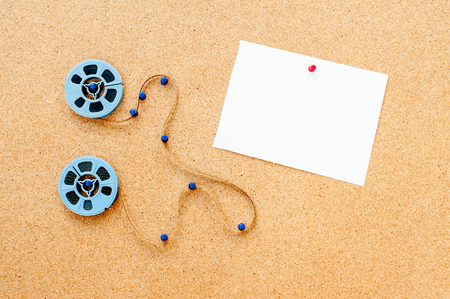 super 8: Two little blue movie reel, filmstrip and white card pinned on cork board
