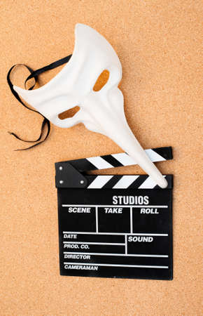 theatre masks: White carnival mask and movie clapper board on cork wooden background