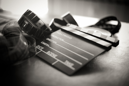 movie reel: Movie clapper board and filmstrip selective focus and vintage black and white Stock Photo