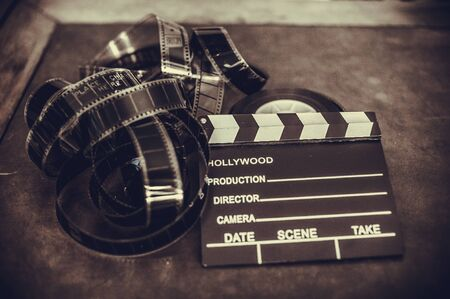 Movie clapper board and filmstrip selective focus and vintage sepia
