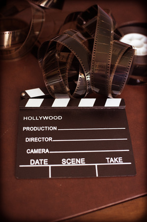 filmstrip: Movie clapper board and filmstrip selective focus and vintage color effect Stock Photo