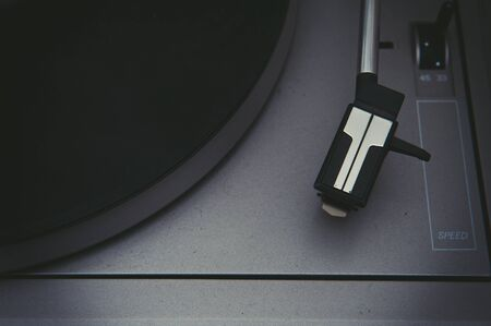 music player: Old dusty turntable detail with vinyl disc and stylus selective focus