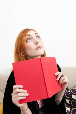 alternative living: Young redhead woman at home with a book looking up