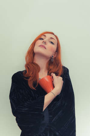 color effect: Young redhead woman with orange mug standing vintage color effect portrait Stock Photo