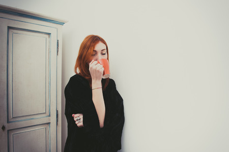 color effect: Young redhead woman drinking with orange mug standing vintage color effect Stock Photo