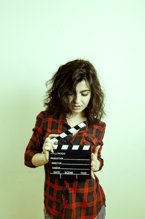 color effect: Young woman in red shirt showing movie clapper board vintage color effect