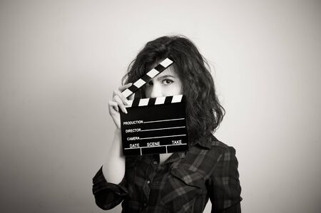 actress: Woman actress eyes portrait behind movie clapper board vintage black and white
