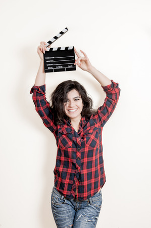 actress: Smiling brunette woman actress with movie clapper board up on white background