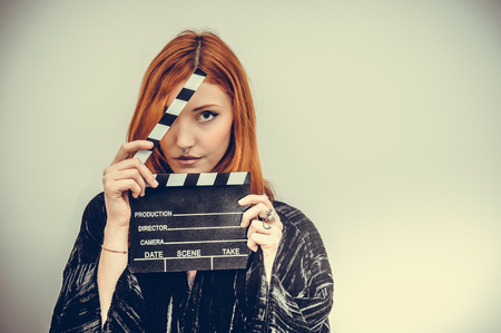 color effect: Pretty redheadn actress with movie clapper board looking at camera, vintage color effect