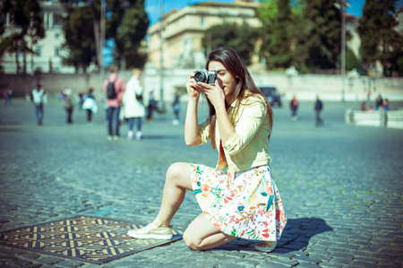 the place is outdoor: Young tourist woman taking picture with vintage camera outdoor in place of Rome, vintage color effect