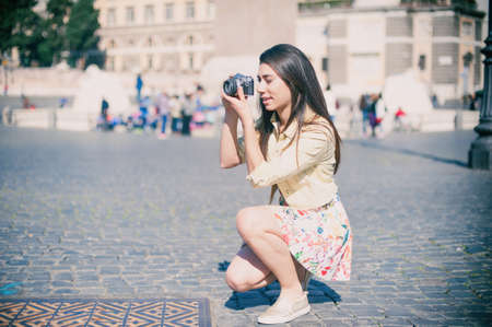 color effect: Young tourist woman taking picture with vintage camera outdoor in place of Rome, vintage color effect