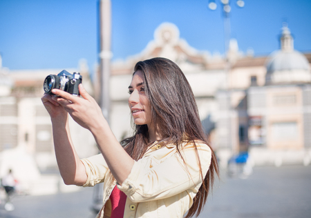 the place is outdoor: Young tourist woman taking picture with vintage camera outdoor in place of Rome Stock Photo