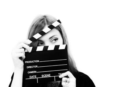 actress: Young woman actress with movie clapper posing isolated in black and white
