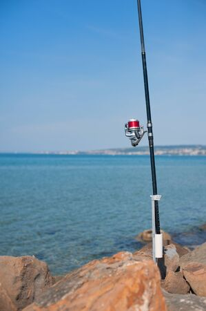 Fishing pole: Fishing pole with red reel detail with blue sea and sky out of focus background