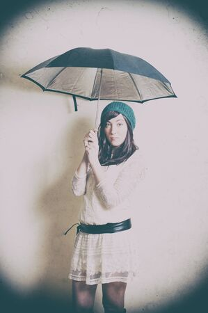70's: Young woman in 70s style portrait with umbrella old vintage image effect Stock Photo