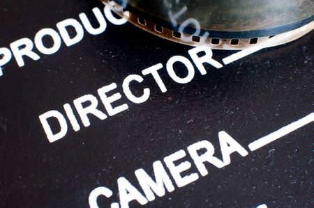 board of director: Movie symbol: detail of movie clapper board with director label and film reel, macro close up selective focus