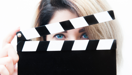 close up eyes: Young blue eyes blonde woman actress close up with movie clapper behind face Stock Photo