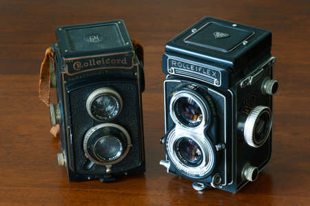 collectible: Vintage collectible couple of bioptical Rolleicord and Rolleiflex camera still life on wooden table Editorial