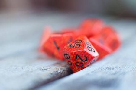 role play: Group of different red role play dice with detail of hundreds percentage dice in selective focus