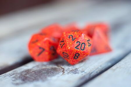 role play: Group of different red role play dice with detail of Icosahedron dice twenty number face in selective focus