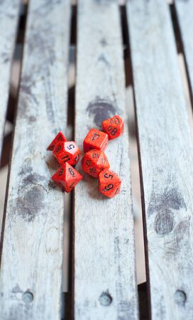 role: Group of different red role play baord game dice close up on wooden table