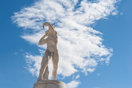 olympic symbol: Rome, Italy - August 6th 2016. Shot putter statue at Stadium of the Marbles with blue sky and clouds in background