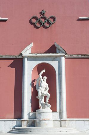 olympic symbol: Rome, Italy - August 6th 2016. Fighter marble statue with olympic game rings symbol Editorial