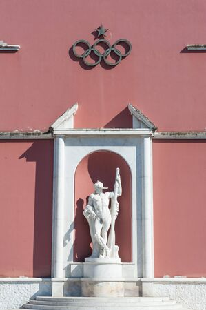 olympic symbol: Rome, Italy - August 6th 2016. Canoeist marble statue with olympic game rings symbol Editorial