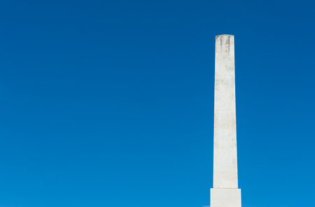 obelisk stone: White marble obelisk on blue clear sky, masculine power and strength concept Stock Photo