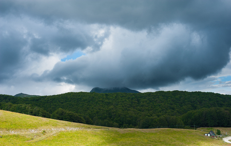 tempest: Green mountain landscape with dramatic dark stormy sky and clouds