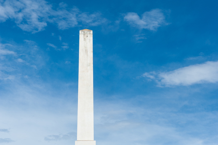obelisk stone: White marble obelisk on blue sky and clouds, masculine power and strength concept Stock Photo