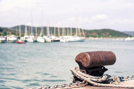Rusted mooring bollard  in dock of harbor pier, rope and sailing boat out of focus in background