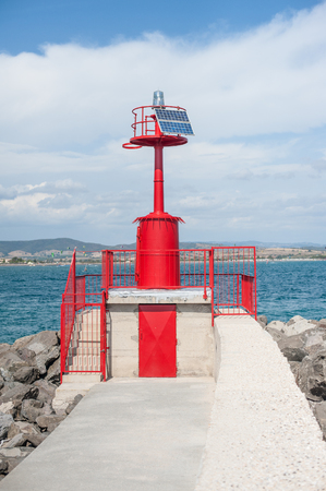 beacon light: Red marine beacon light with solar panels energy on harbor dock, sea and coastline in background