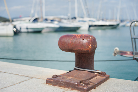 Rusted mooring bollard  in dock of harbor pier,  sailing boat out of focus in background