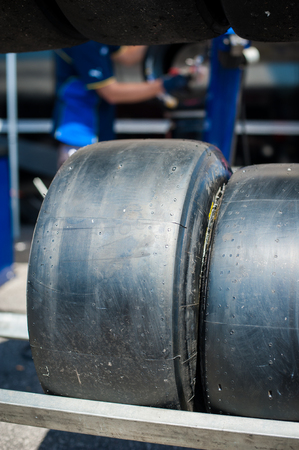 motorsport: Motorsport slick tire close up with blurred man working in background
