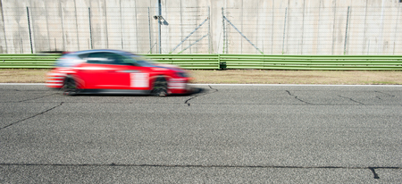 motorsport: Blurred red car racing on track during motorsport event