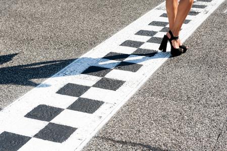 sexy füsse: Frau sexy Füße mit hohen Absätzen auf Motorsport Chekered Asphalt Linie