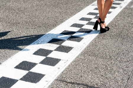 pies sexis: Woman sexy feet with high heels on motorsport chekered asphalt line
