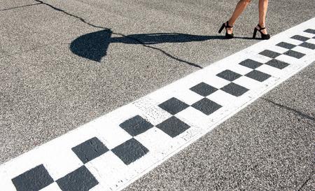 pies sexis: Pies de la mujer sexy con tacones altos en los deportes de motor chekered línea de asfalto