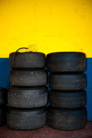 motor sport: Tire set inside motor sport circuit pit, yellow and blue wall