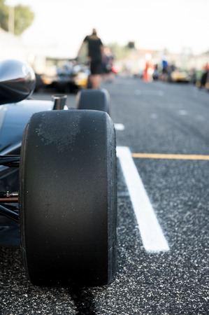 Black slick motor sport tire close up, car on starting grid with out of focus background