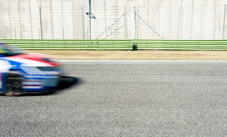 motorsport: Blurred blue and red car nose racing on track during motorsport event coming into the image from left Stock Photo