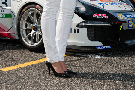 starting line: Vallelunga, Rome, Italy. September 10th 2016.  Grid girl with black high heels legs and Porsche Carrera on starting line
