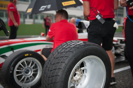 starting line: Vallelunga, Rome, Italy. September 10th 2016. Formula 4 Championship, Mechanic working on car wet racing tire on starting line