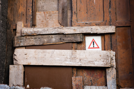 rickety: Warning symbol on old ruined door closed and blocked with wooden plank Stock Photo