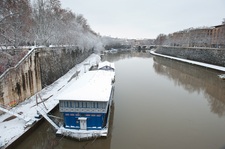Rome river Tiber in winter snow landscape with boat building and trees Stock Photo