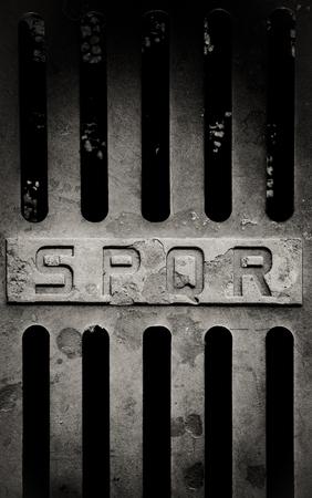 spqr: Hierro viejo detalle de la tapa de alcantarilla romana con la muestra spqr Foto de archivo