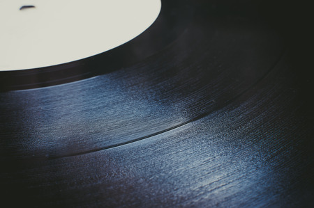 grooves: Lp record section extreme close up, black grooves detail and white defocused label